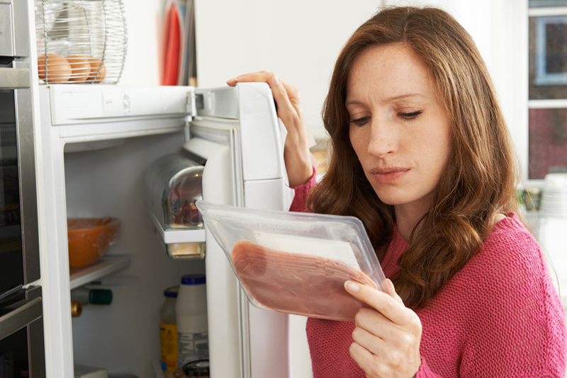 Concerned Woman Looking At Pre Packaged Meat Image